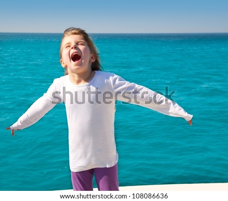 excited kid girl sailing in a boat open arms at the sea - stock photo