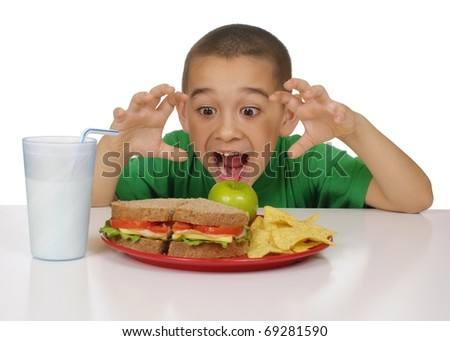 Excited kid ready to eat a healthy sandwich meal, meat sandwich on whole wheat bread, tortilla chips, and a green apple - stock photo