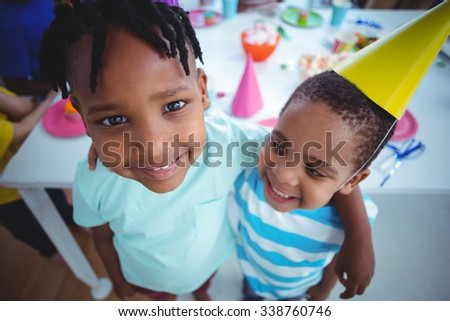 Excited kids enjoying a birthday party wearing birthday hats - stock photo