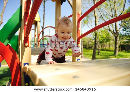 Excited little baby girl crawling on playground