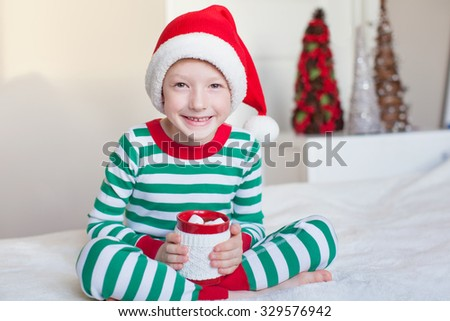 excited little boy in santa's hat and cozy pajamas holding cup with hot cocoa enjoying christmas time at home - stock photo