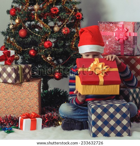 Excited little boy opening christmas present in front of the fir tree.  New Year's holidays.
