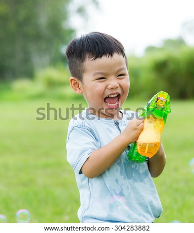 Excited little boy play with bubble blower at outdoor - stock photo