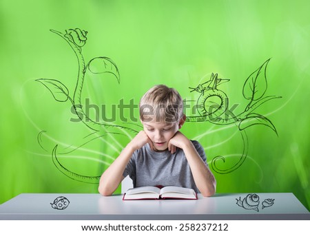 Excited little boy reading the book in green room - stock photo