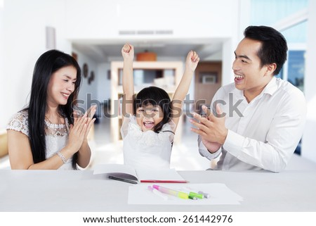 Excited little girl expressing her happiness after finishing her schoolwork and get appreciate - stock photo
