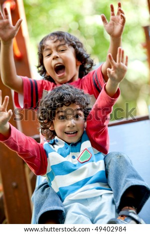 Excited little kids playing at the park - stock photo