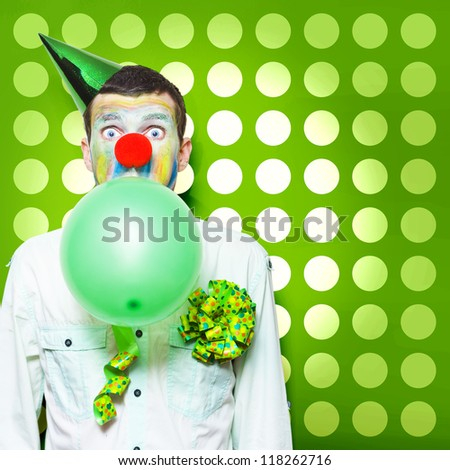 Excited Male Clown With Colourful Face Paint Blowing Up A Green Balloon While Having Fun Celebrating Kids Birthday Parties - stock photo