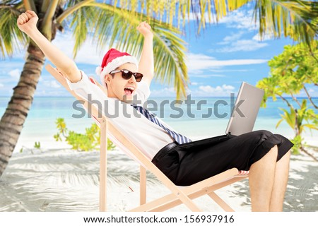 Excited male with santa hat sitting on a beach chair and working on a laptop, on a tropical beach