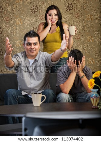 Excited man and woman with distraught son watching television - stock photo