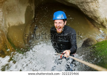 Excited man climbing cliff in canyon with rope.