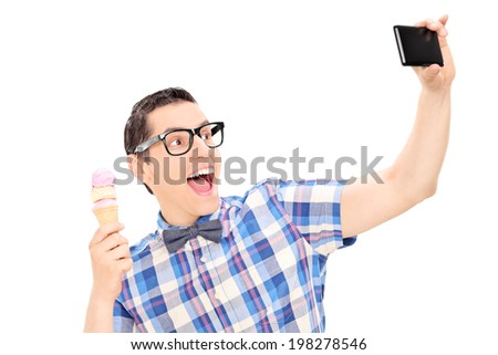 Excited man holding ice cream and taking selfie isolated on white background - stock photo