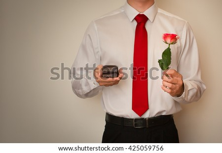 Excited man in dress shirt and red tie, holding a wedding ring box and red rose about to propose. - stock photo