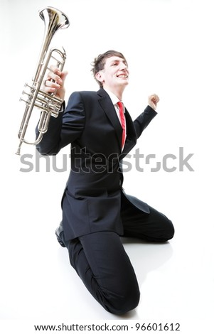 Excited man kneeling with trumpet in hand and screaming. Isolated on white background.