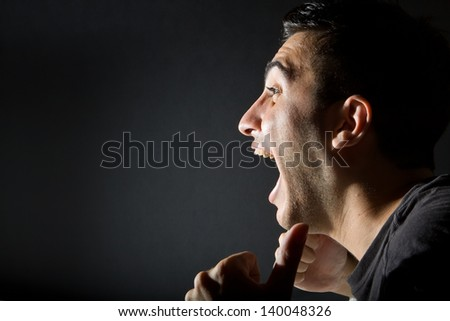 Excited man on black background - stock photo