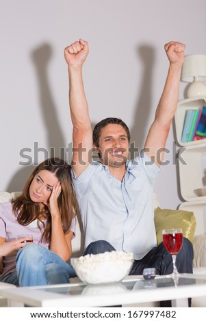 Excited man watching TV with wine glass and popcorn besides a bored woman on sofa at home - stock photo