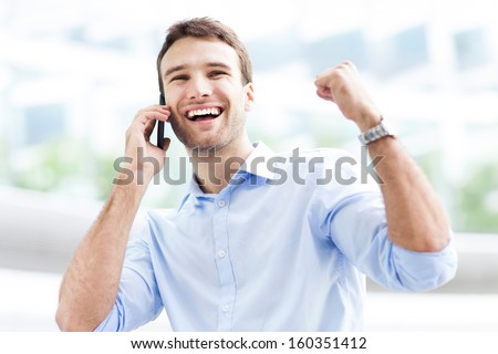Excited man with mobile phone - stock photo