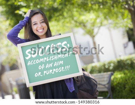 Excited Mixed Race Female Student Holding Chalkboard With Success and the Definition Written on it. - stock photo