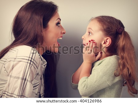 Excited mother and surprising kid girl looking on each other with opened mouth. Toned vintage portrait - stock photo