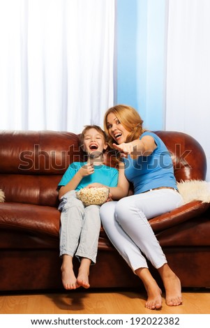 Excited mother pointing at TV with laughing son - stock photo