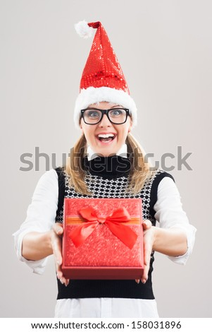 Excited nerdy woman is holding Christmas present,Christmas present - stock photo