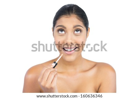 Excited nude brunette holding lip gloss on white background