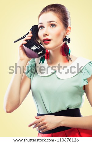 Excited pin-up girl using a shoe like a telephone holding it near her face and talking, yellow background. - stock photo