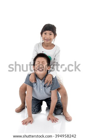 Excited pretty girl enjoying riding on boy isolated on white