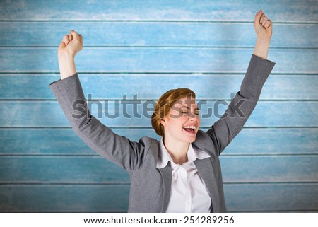 Excited redhead businesswoman cheering against wooden planks - stock photo