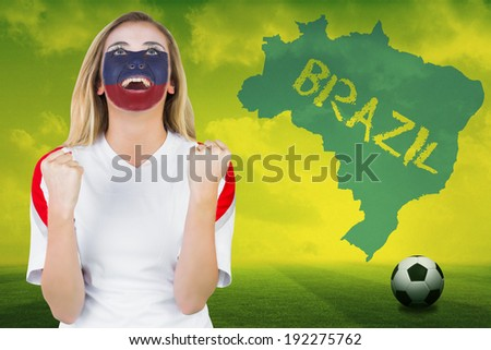 Excited russia fan in face paint cheering against football pitch with brazil outline and text - stock photo