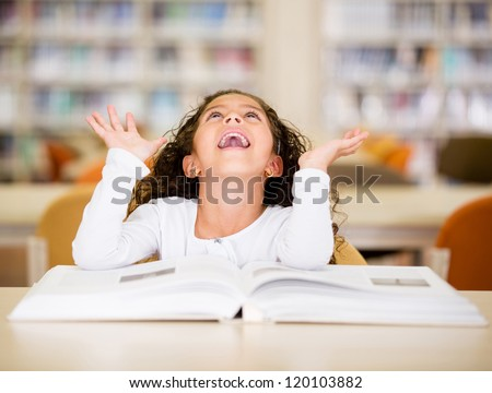Excited schoolgirl at the library reading a book - stock photo