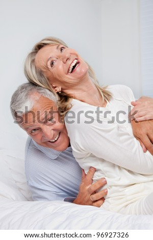 Excited senior couple laughing together on bed - stock photo