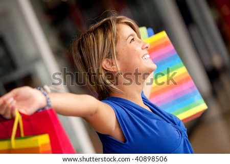 excited shopping woman with bags at a mall