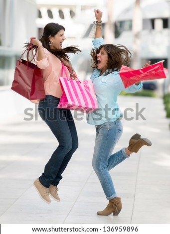 Excited shopping women jumping and holding bags
