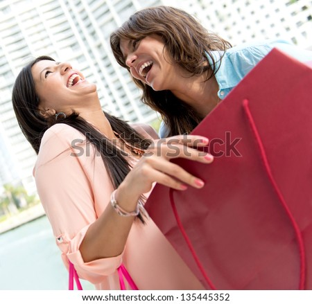 Excited shopping women looking at their purchases - stock photo