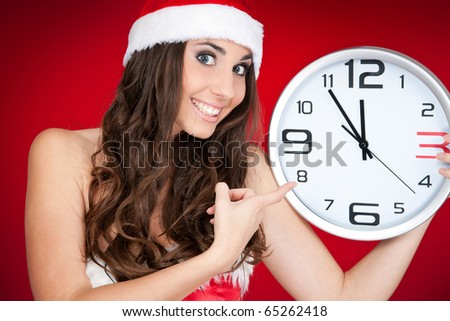 excited smiling girl with santa hat  pointing at clock - stock photo