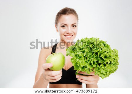 Excited smiling sports woman showing lettuce and green apple isolated on a white background