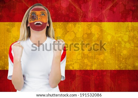Excited spain fan in face paint cheering against spain flag in grunge effect