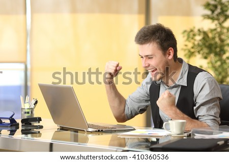 Excited successful businessman working on line with a laptop in a desktop at office - stock photo