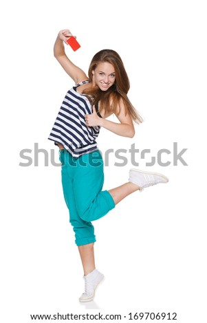 Excited teen girl  in casual summer clothes in full length showing blank credit card, over white background - stock photo