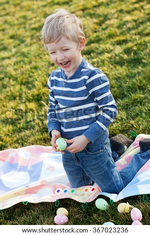 excited toddler coloring eggs at easter time in the park