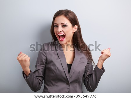 Excited winner business woman with opened mouth. Happy young satisfacted female showing the gesture yes by fists on blue background