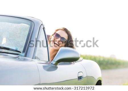 Excited woman enjoying road trip in convertible against clear sky