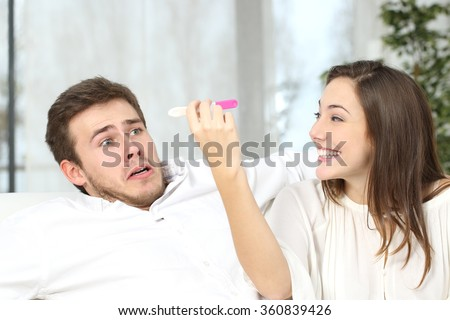 Excited woman getting pregnant to keep to her scared not ready partner at home interior - stock photo