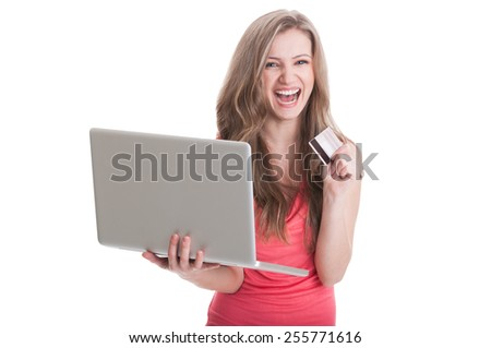 Excited woman holding a laptop and credit card while smiling - stock photo