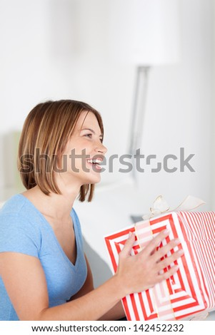 Excited woman holding a large gift box gift wrapped in striped paper as she celebrates a happy occasion - stock photo