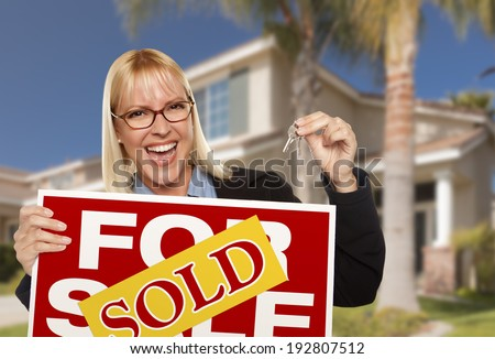 Excited Woman Holding House Keys and Sold Real Estate Sign in Front of Nice New Home. - stock photo