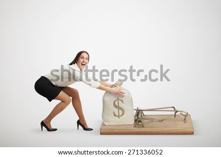 excited woman in formal wear reaching her arms to take bag with money in big mousetrap over light grey background - stock photo