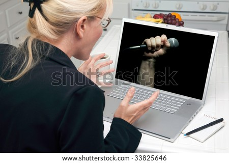 Excited Woman In Kitchen Using Laptop for Freedom of Speech. Screen image can easily be replaced using the included clipping path. - stock photo