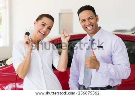 excited woman just bought a new car from dealership - stock photo