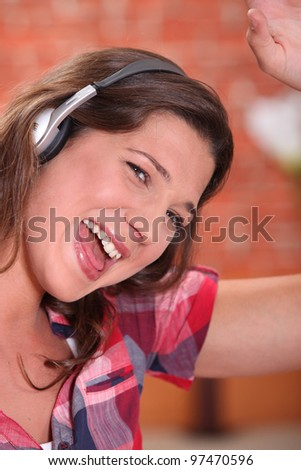Excited woman listening to music through headphones - stock photo